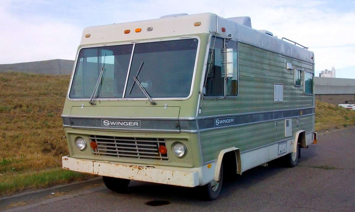 an old boxy motorhome, green paint on the sides, large front windows, on the side of a road in a field somewhere