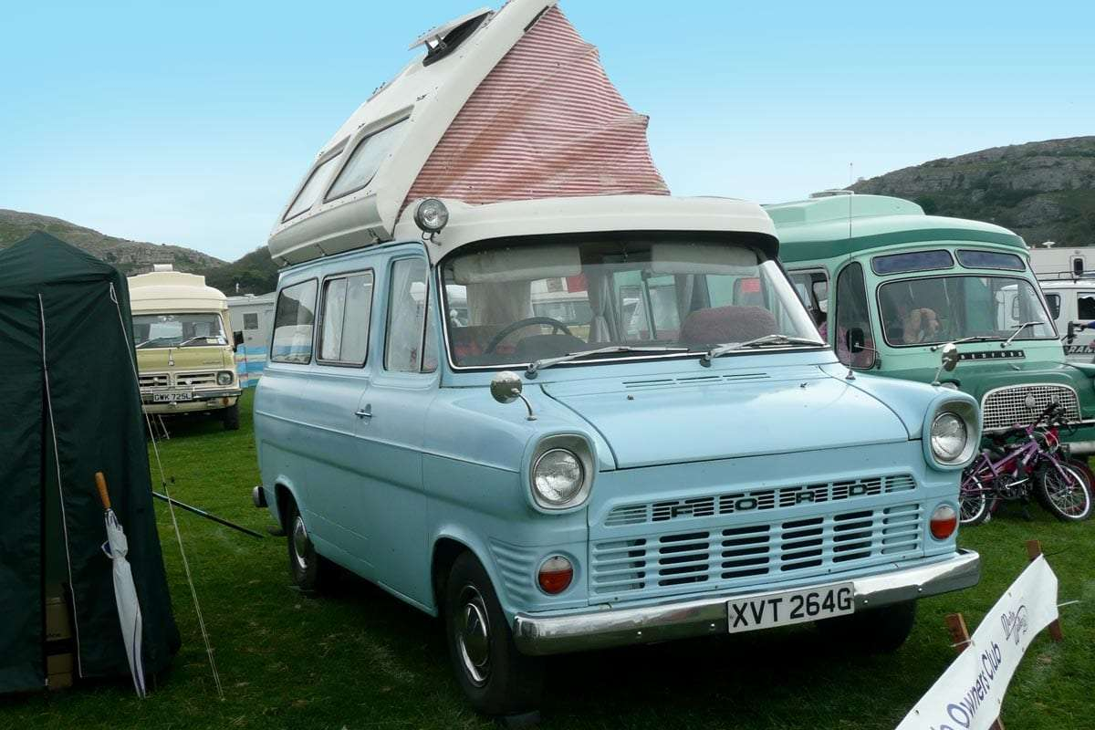 a baby blue old ford van with a poptop roof, a true classic