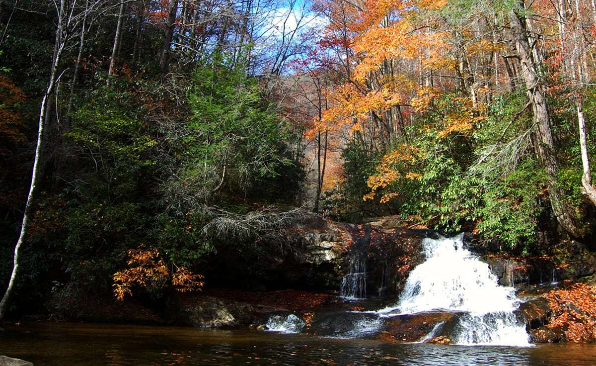 a small waterfall, beautiful, surrounded by changing leaves