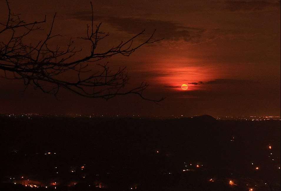the moon rises red over the mountains of Georgia, the lights of civilization glimmer below
