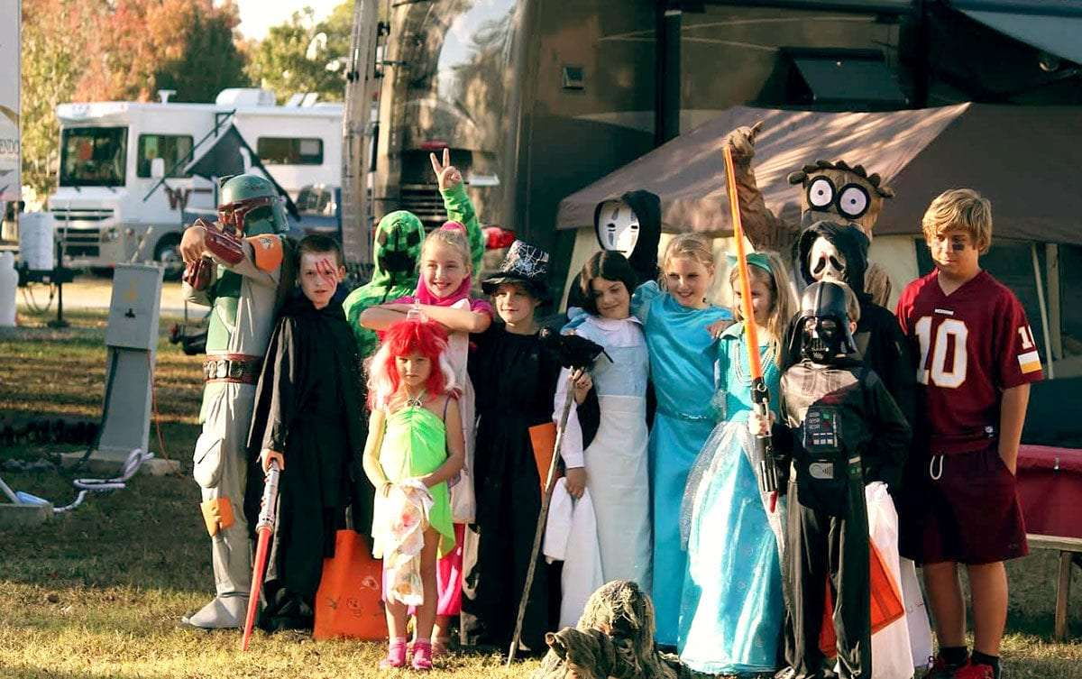 kids dressed up for halloween, all standing in front of RVs