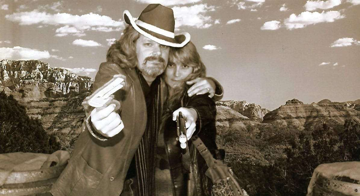 Jenn and Greg dressed up like wild west outlaws against a backdrop resembling the mountains of Utah
