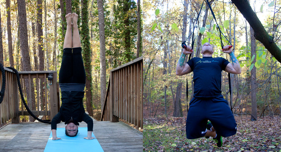 a woman balances herself on her head on a yoga mat in the forest, a man pulls himself up via exercise equipment