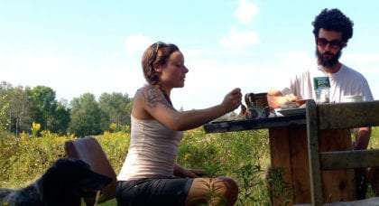 a young man and woman eating dinner outside on their farm
