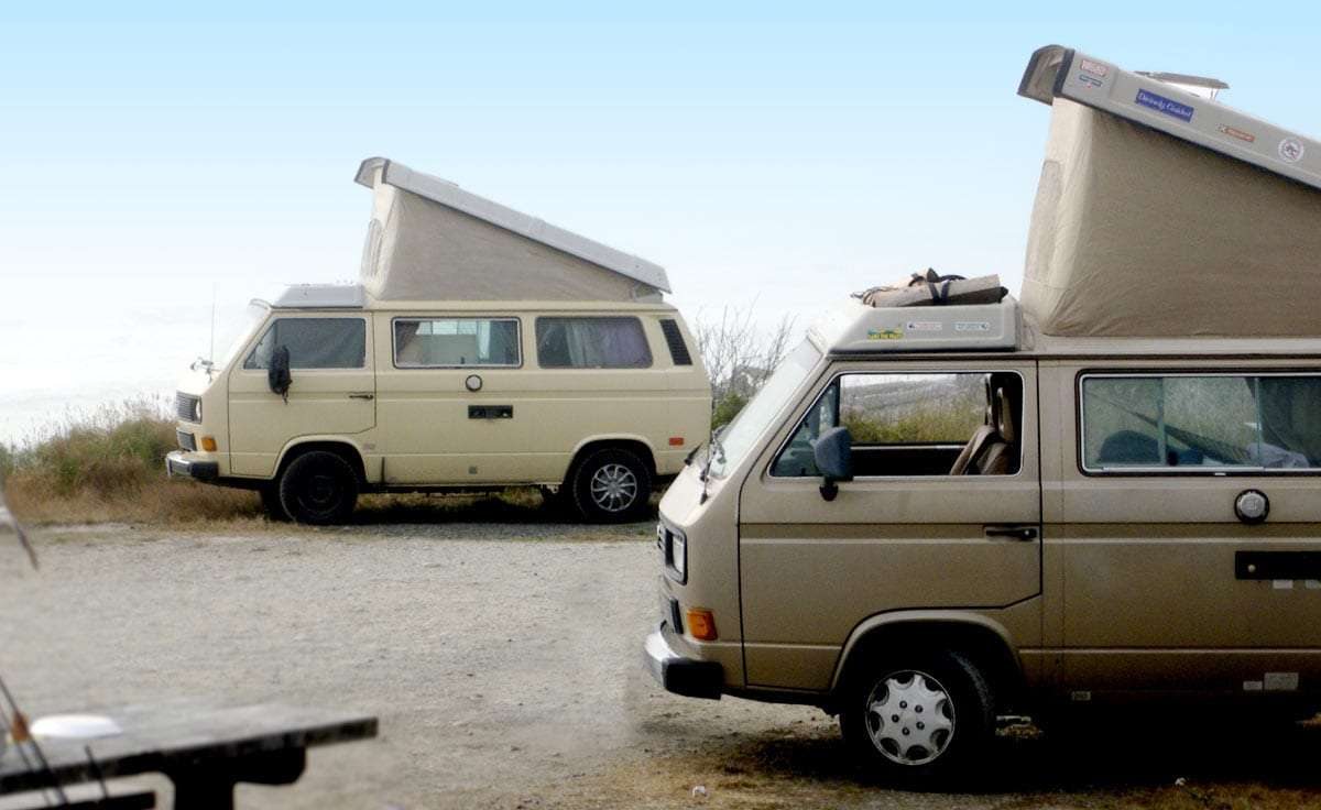 two vans with pop tops parked at the beach