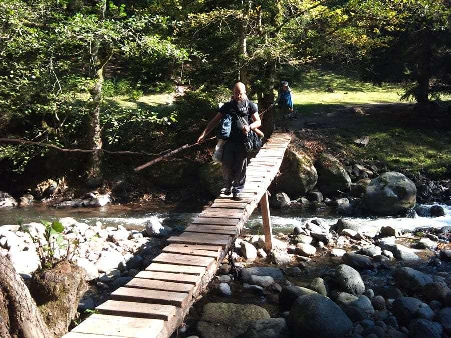 A hitchhiker balances over a thin, seemingly rickety bridge over a stream