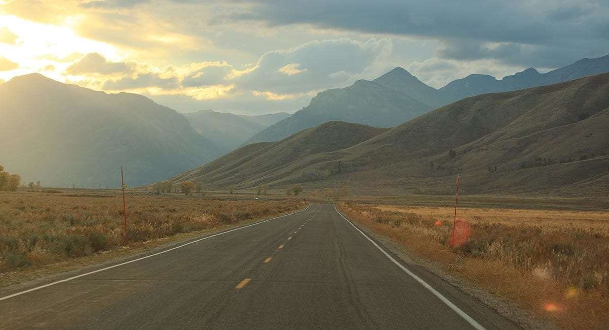 a road triangles into the horizon, mountains and the sunshine of a new promise all that the distance holds