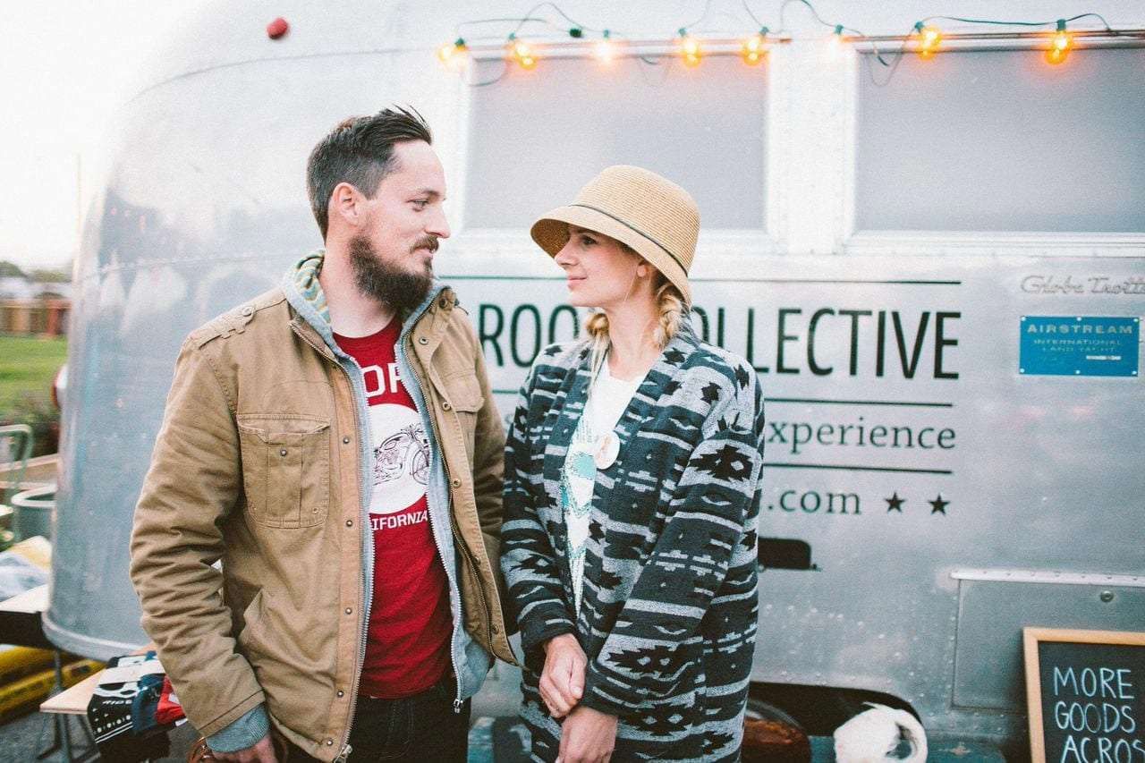 Travis and Lauren of Small Room Collective looking adoringly at one another in front of their Airstream
