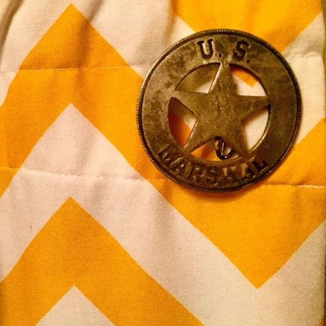 a US Marshall's badge, star inside of a circle, pinned to a yellow and white chevron curtain