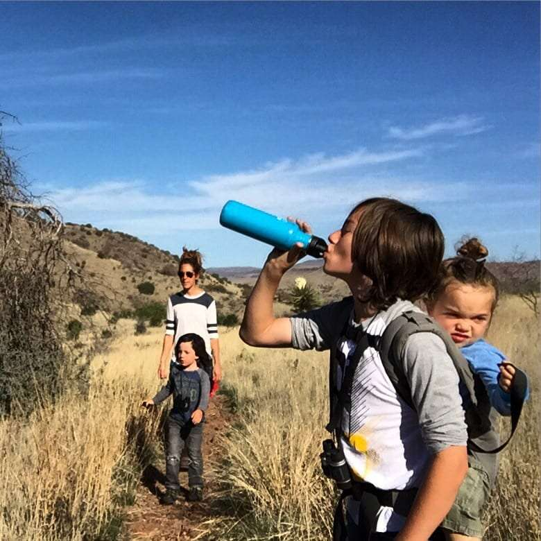 A young family hiking a desert mountain trail