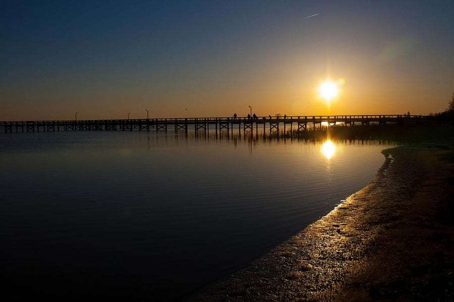 the sun setting over a pier, the Gulf of Mexico