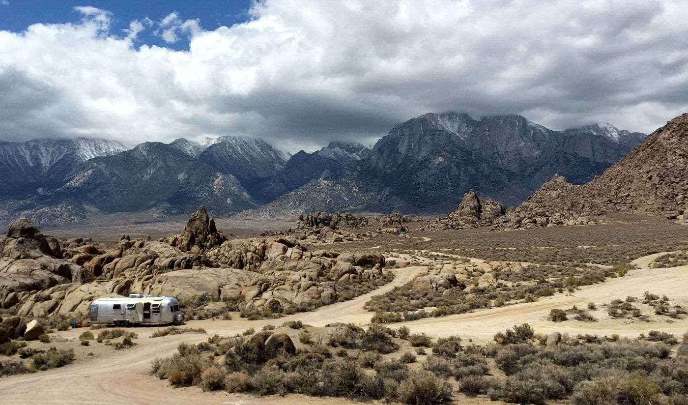 an Airstream travel trailer shining silver against the free camping of the boulders of Alabama Hills near Lone Pine, California