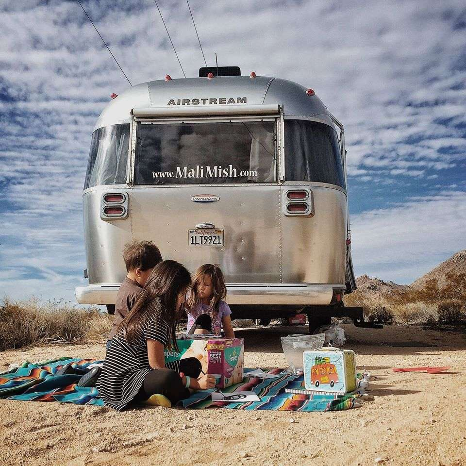 three young children play on a blanket in front of an airstream travel trailer - mali mish