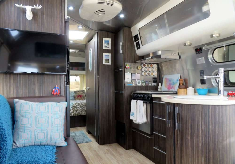 the interior of a new airstream travel trailer, showing the kitchen, blue pillows on a couch, a television, and peering down the hallway toward a bedroom.