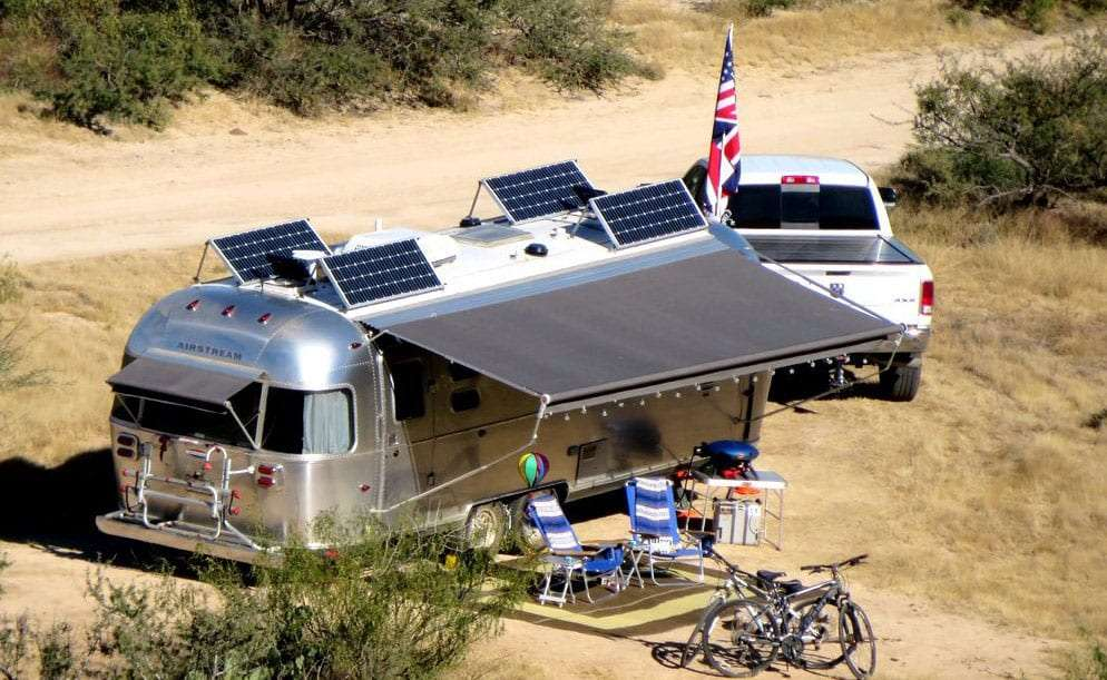an Airstream parked in a campground with the awning out, solar panels facing the sun