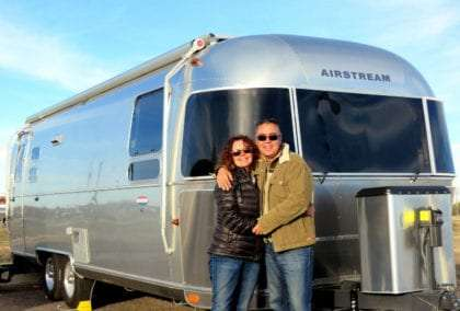 a couple in cold weather clothing standing in front of a brand new airstream travel trailer