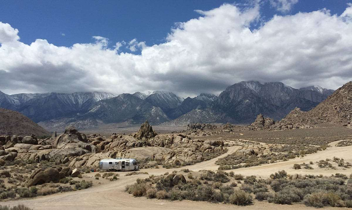 an airstream parked amongst the alabama hills, the eastern sierras, topped in clouds, rise in the background