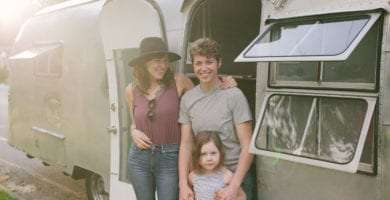 three young ladies, two mamas and their daughter, standing in front of their vintage 50s Airstream