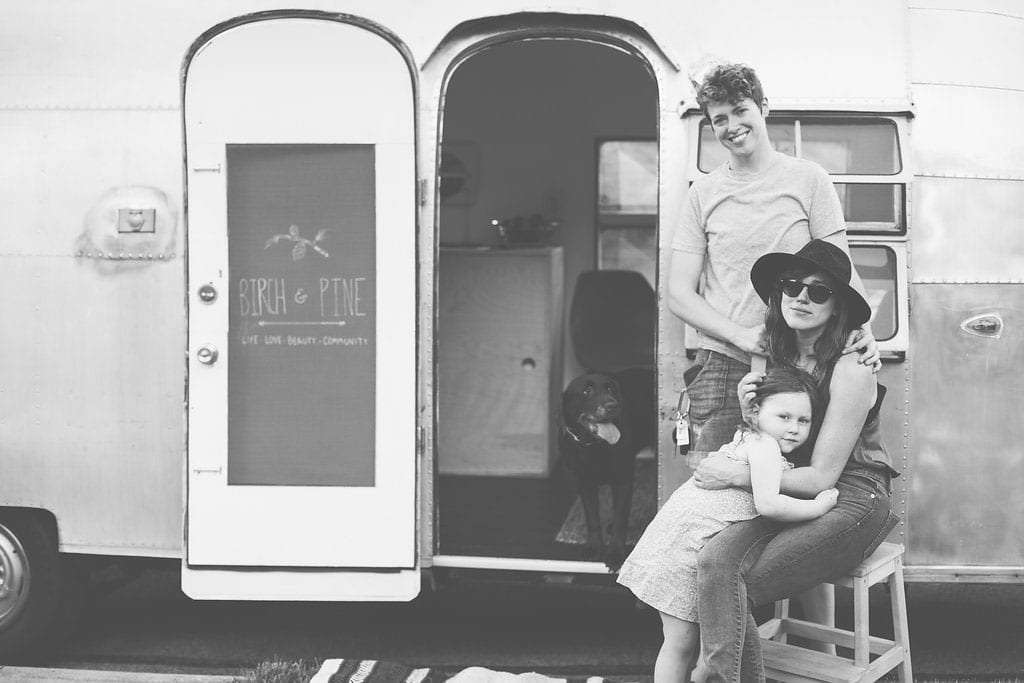 a black and white photo of three ladies, two women in love and their young daughter, the door to the travel trailer reads Birch and Pine