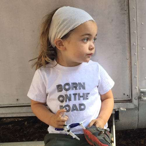 a toddler wearing a shirt that reads born on the road while sitting on an airstream stoop