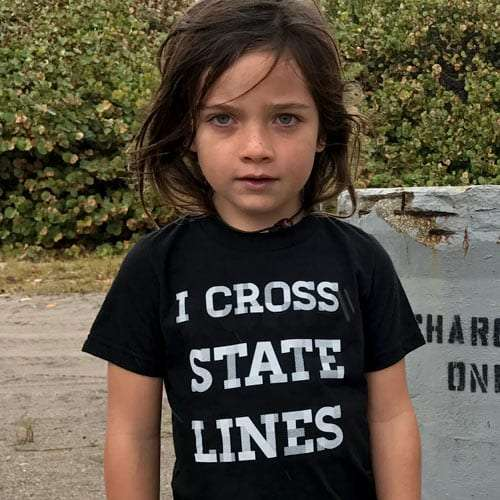 a young boy wearing a shirt that reads i cross state lines