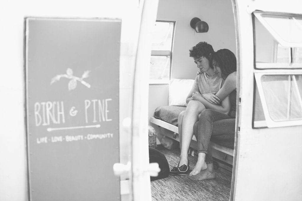 two women in an embrace, seen through the door of an Airstream travel trailer