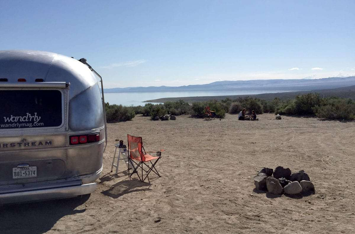 the back of an airstream, some camping chairs, a stone fire pit and an expansive lake beyond it all
