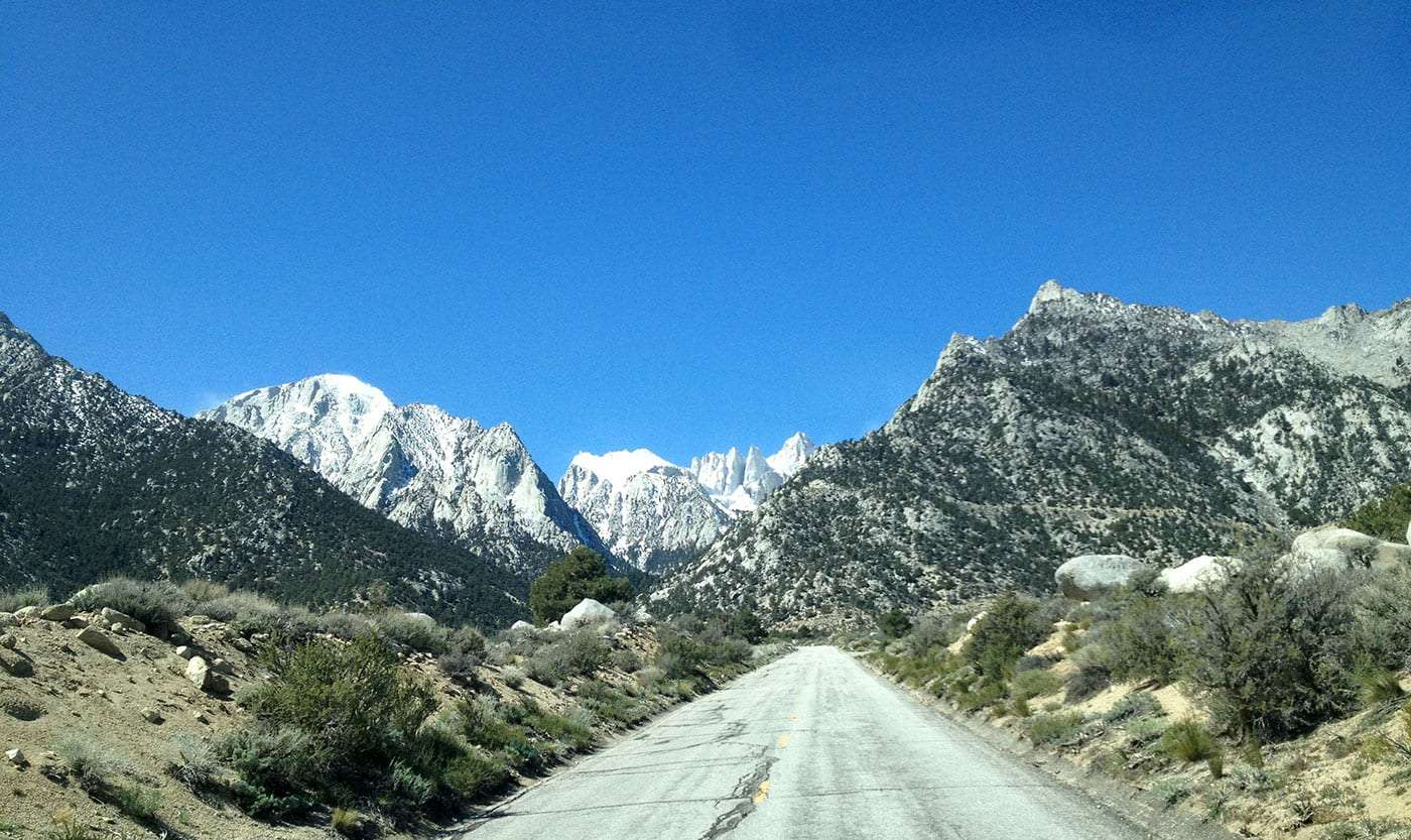 snow covered Mt. Whitney and her fellows rise above a crumbling road