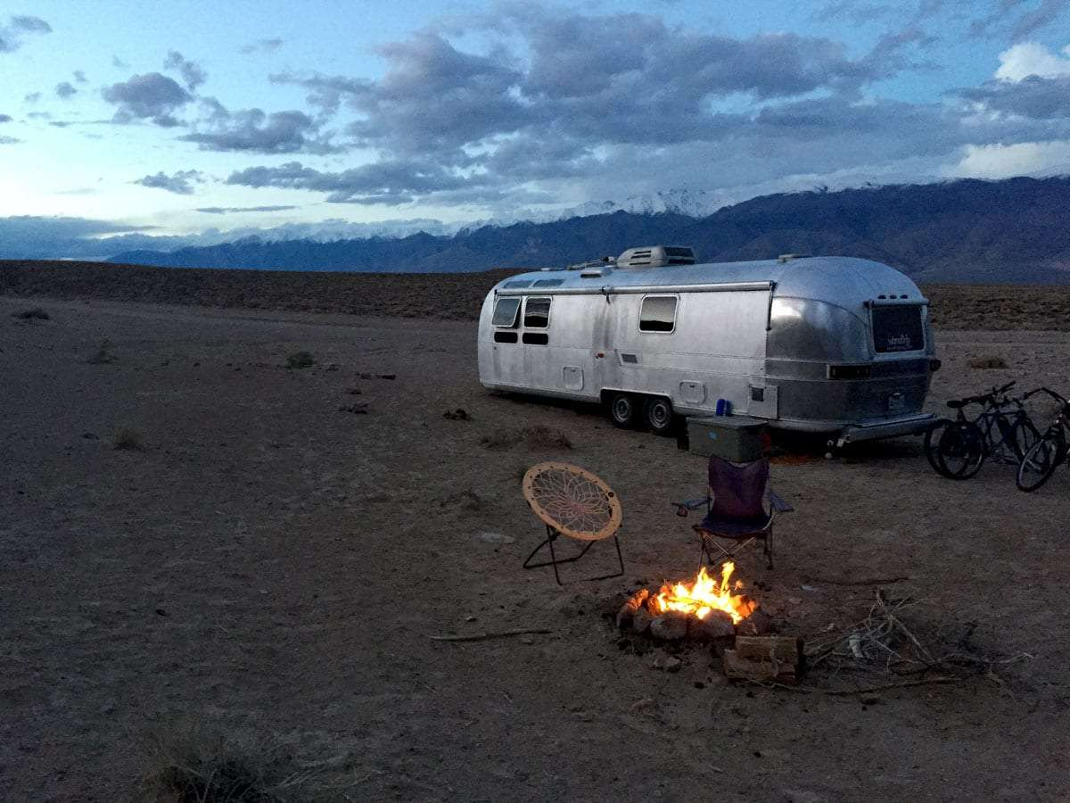 an airstream parked in the desert, a fire blazes in the foreground, snow covered mountains in the distance