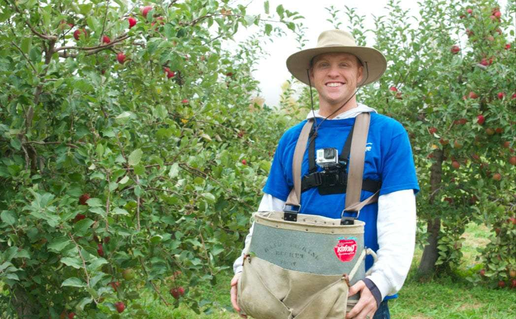 Heath wearing an apple picking bag