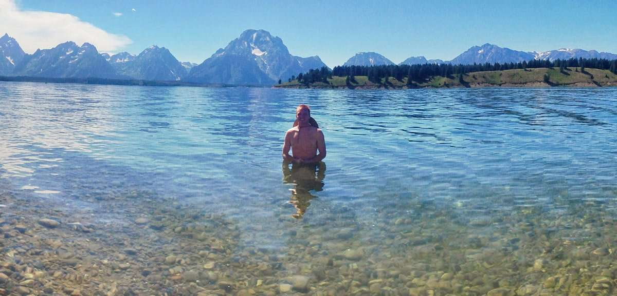 Heath swimming in a large lake, towering mountains behind him.