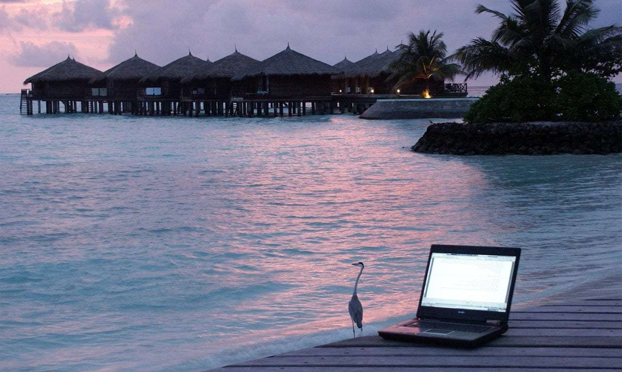 a laptop on a pier near a beach town