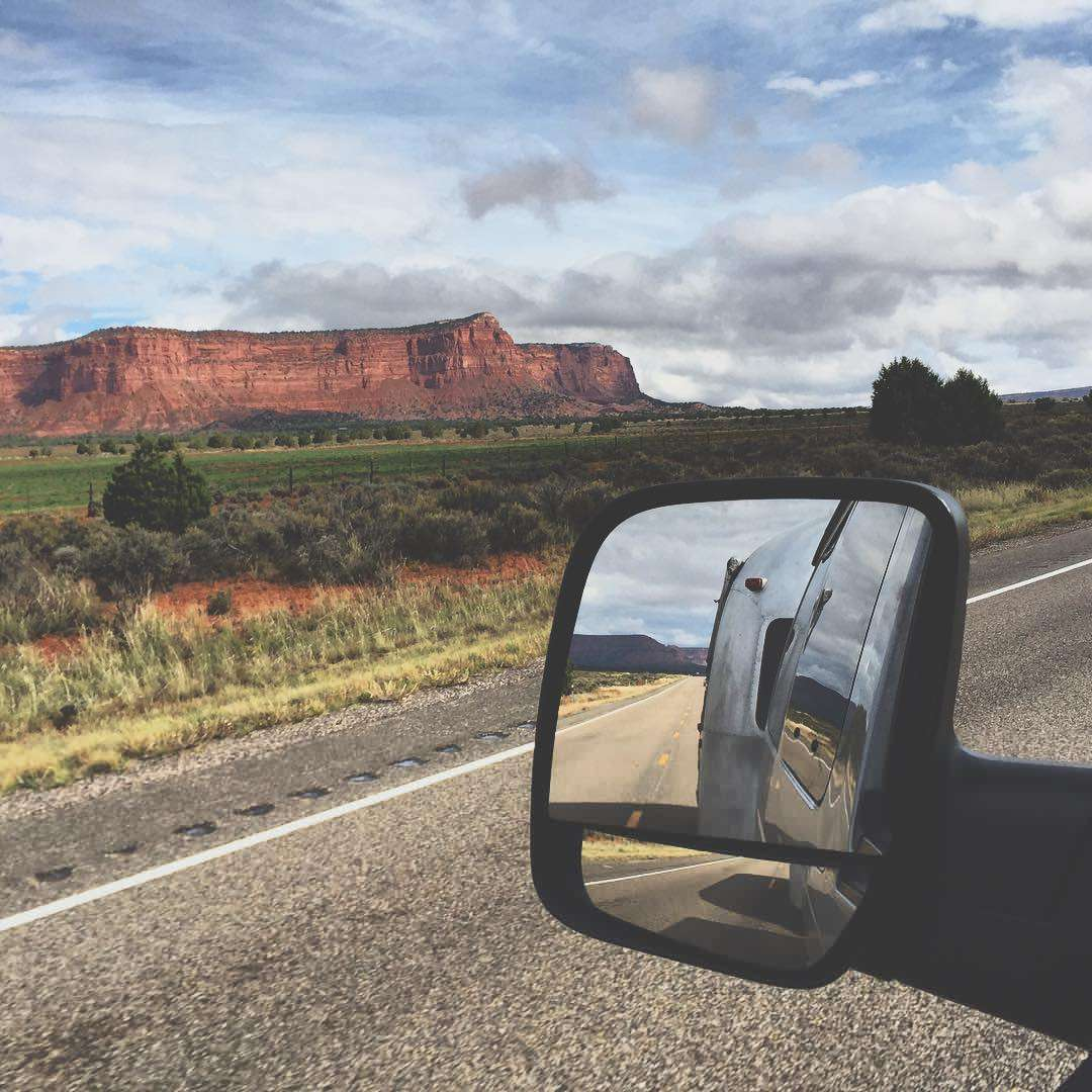 mountains and an airstream, reflected in a van's driver side mirror