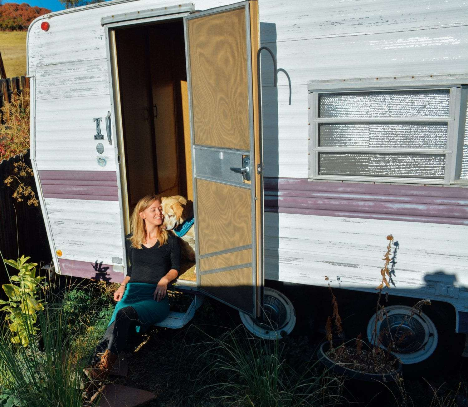 a woman and her dog snuggle in the doorway of a small camping trailer
