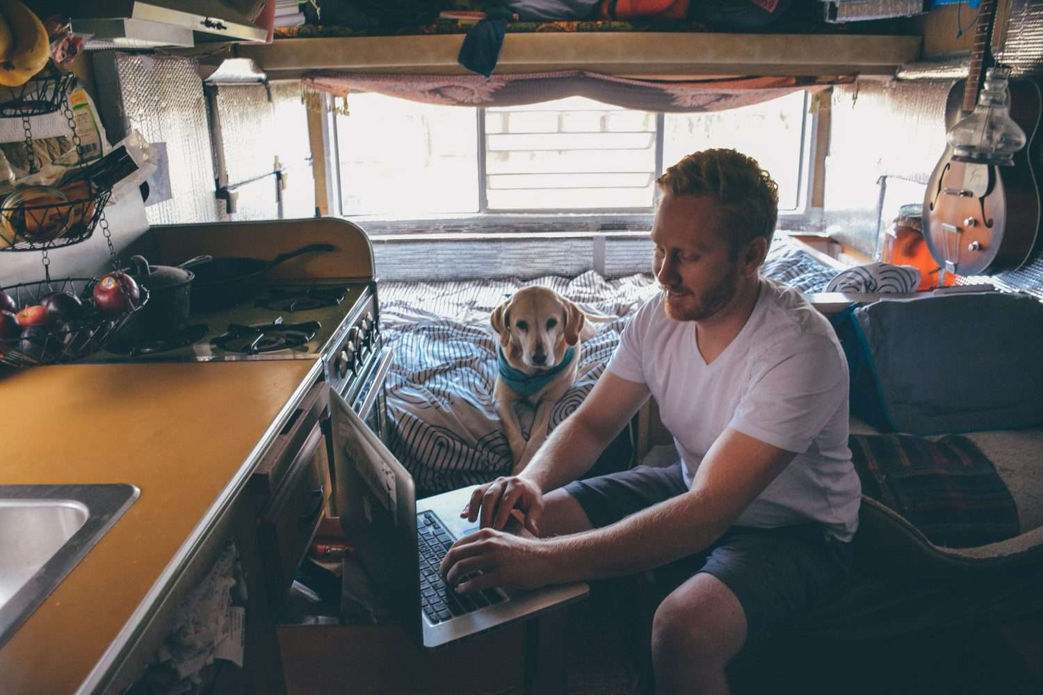 a man works on a laptop from his camper
