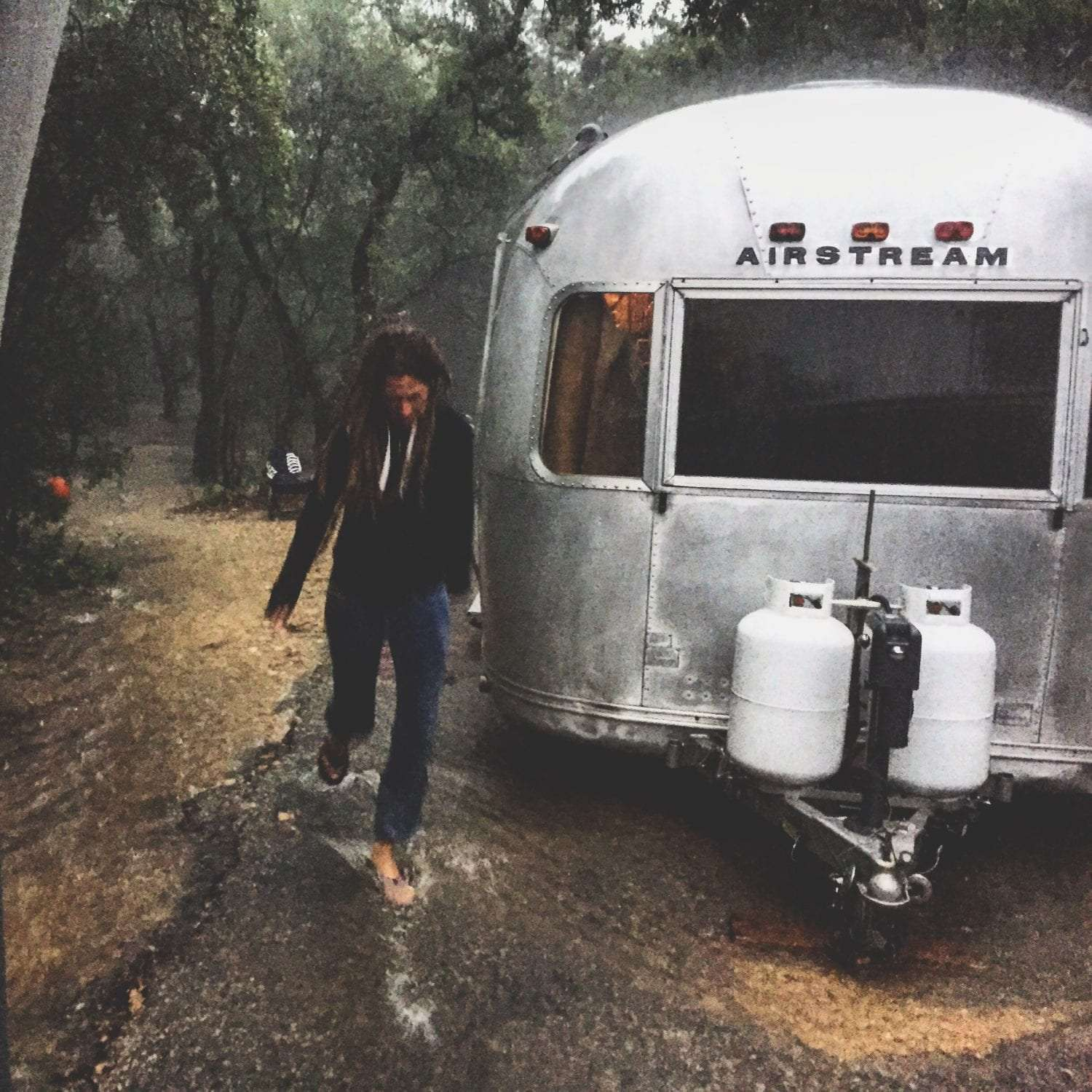 A lovely young woman in a black hoodie runs through the rain in a storm, her airstream in the background