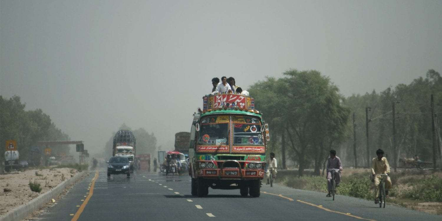 a road in pakistan full of diverse traffic, from pedestrians to cyclists, interesting buses and more