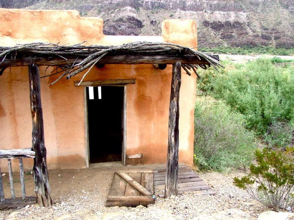 the door has fallen off, and darkness abounds within a small adobe house
