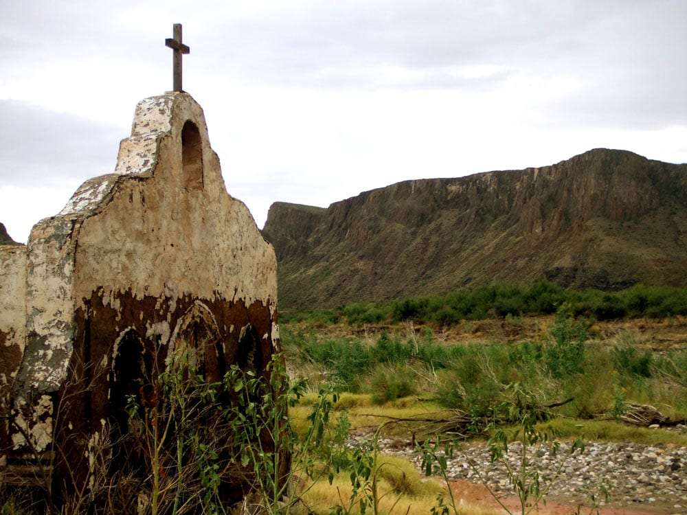 part of the Contrabando movie set, a weathered adobe building, meant to look like a church, holds a cross high into the cloudy west texas sky