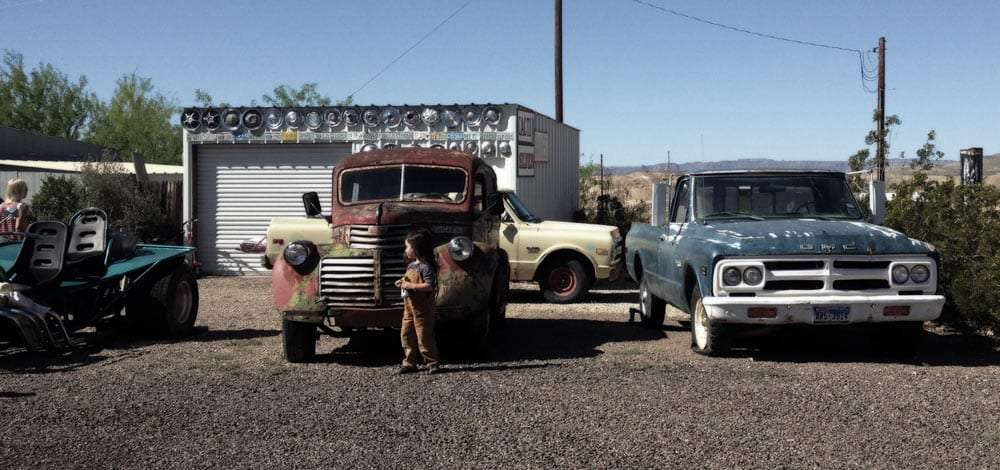 rusty old cars, a young boy walks amongst them interested