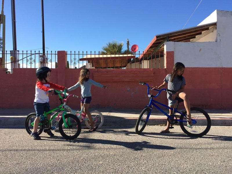 three children on bicycles