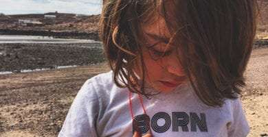 a young boy wears a shirt that reads Born on the Road