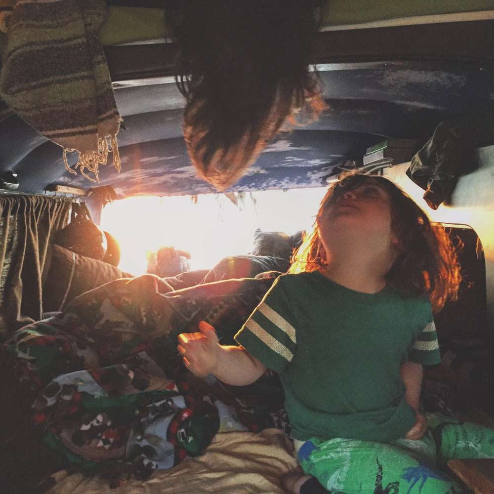 two boys waking up to the sunrise in a VW campervan