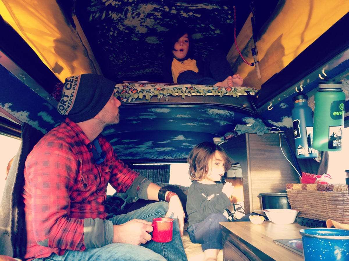 a father and his two younger sons eat breakfast in their Volkswagen Bus Riviera Campgwagen