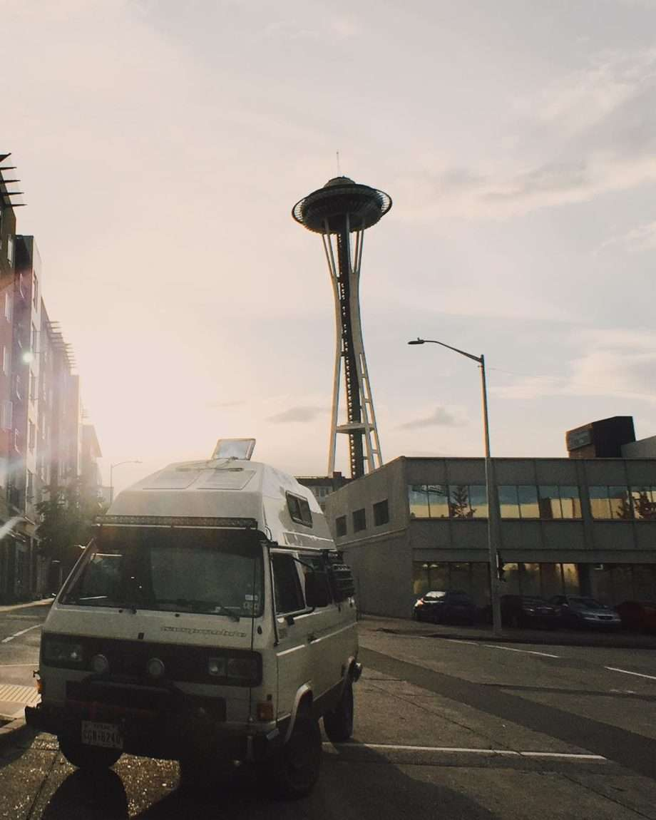a Volkswagen Vanagon parked in front of the Space Needle.