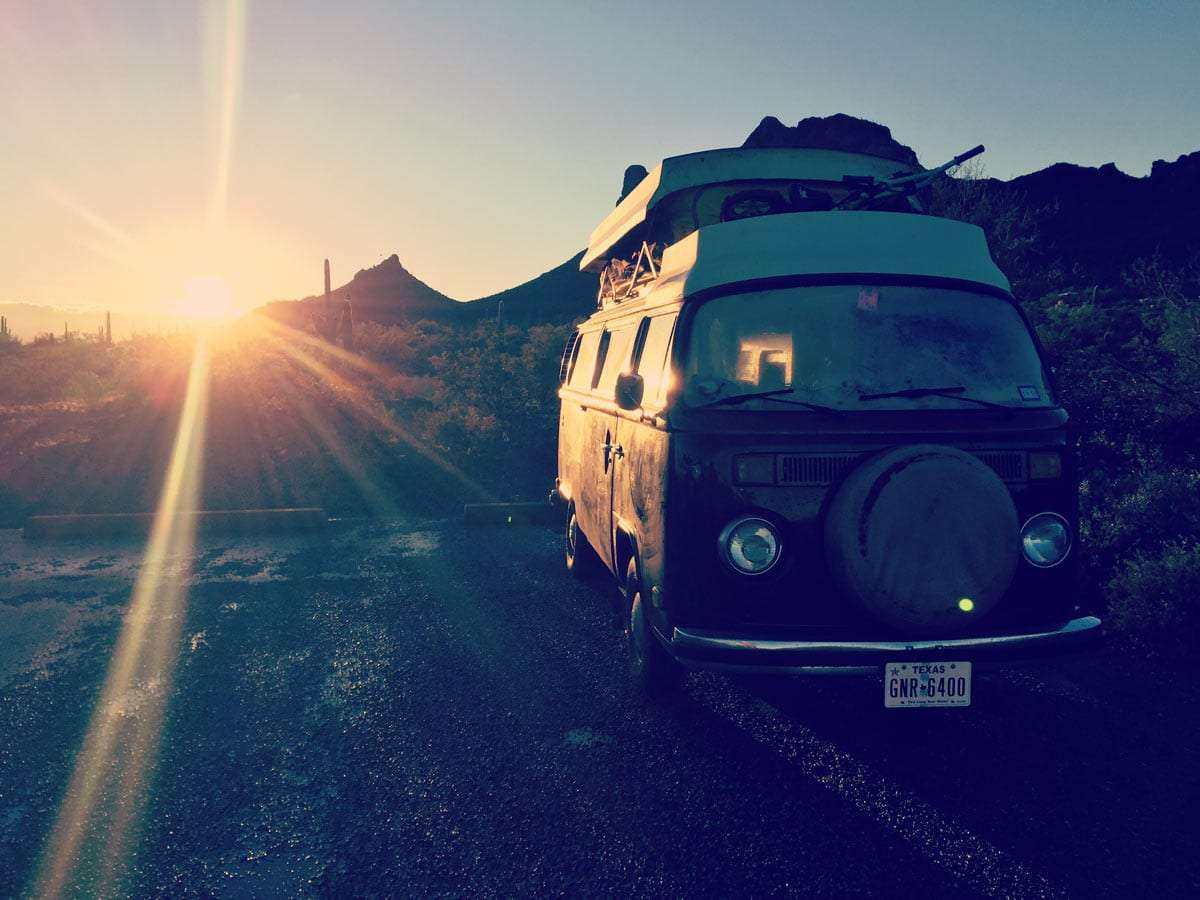 a volkswagen bus in the rising sun