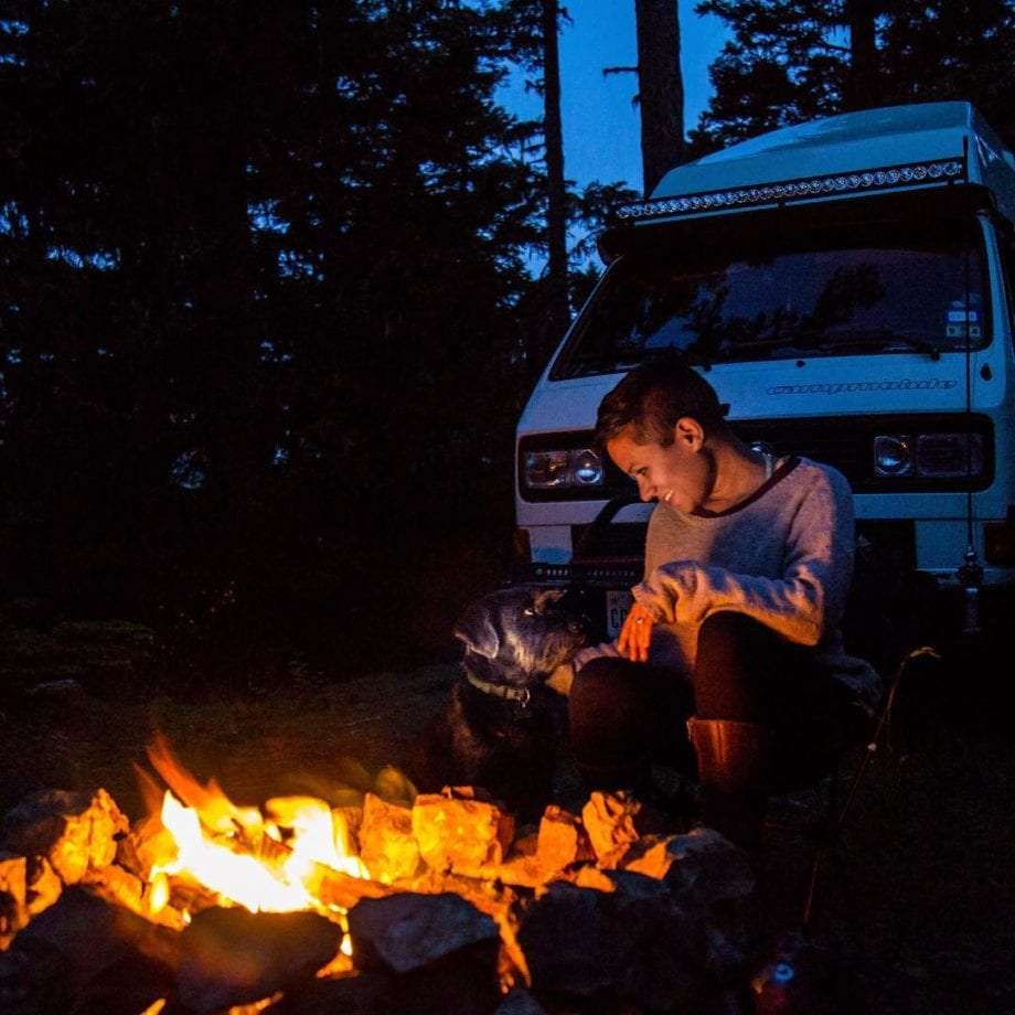 a young woman sitting near a campfire, her vanagon behind her