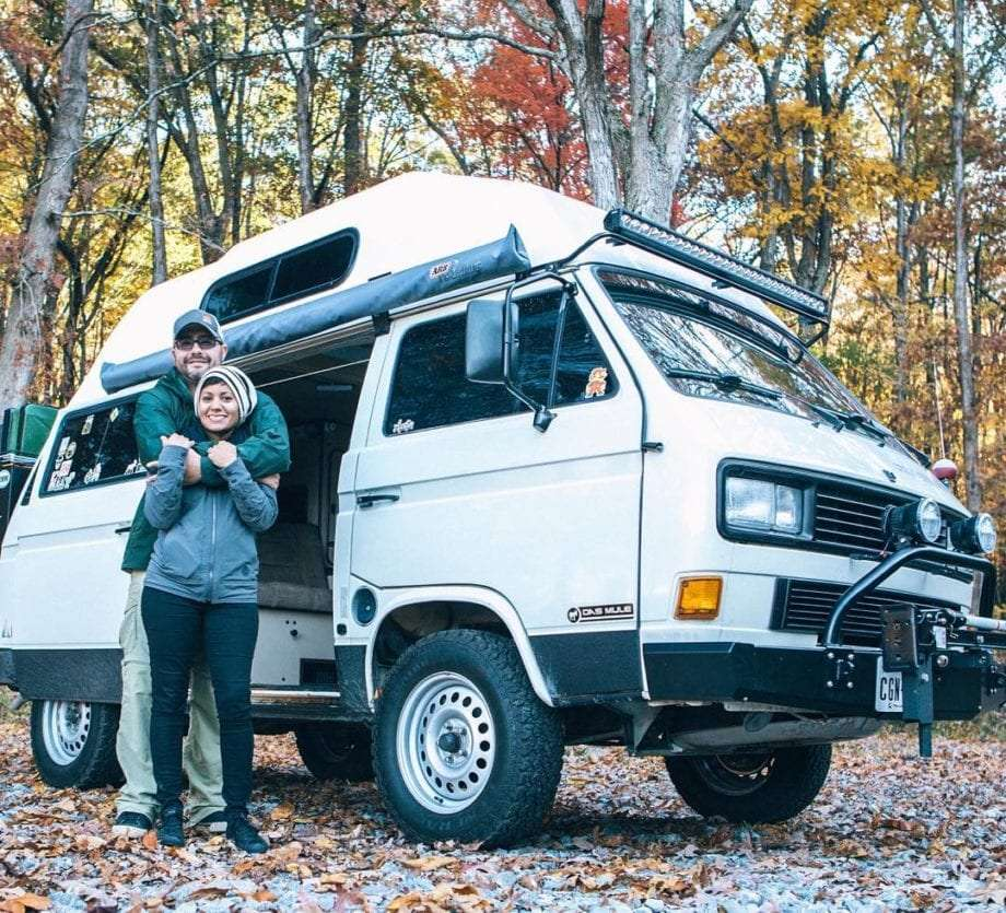 a couple stands in the forest in front of their VW Vanagon