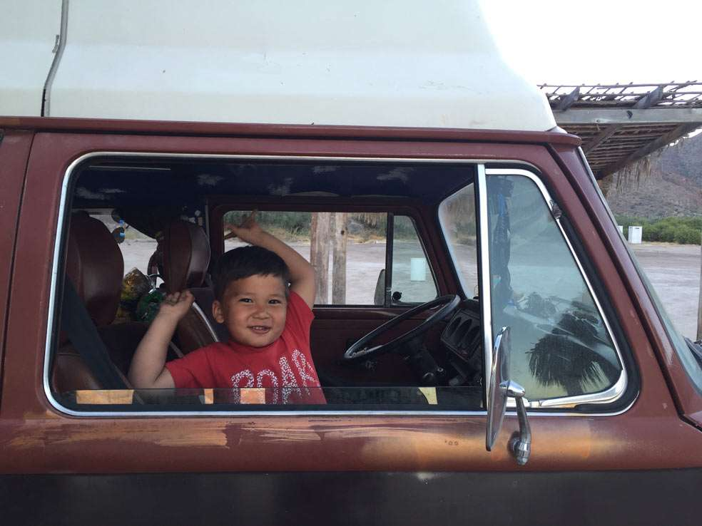a young boy sits in the shotgun seat of a 1978 Volkswagen Bus, Champagne Edition, Riviera Campwagen