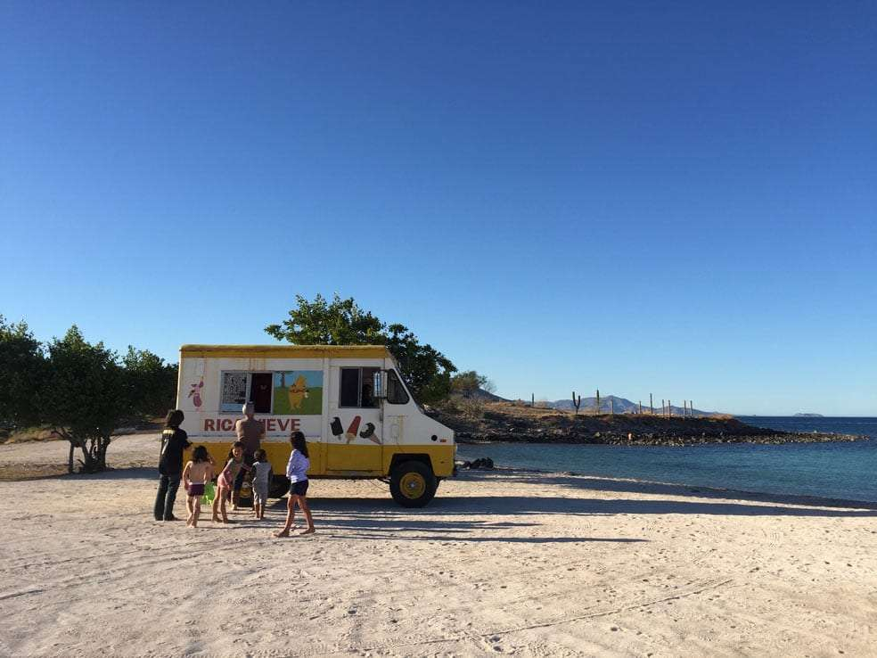 an old truck reads rica nieve, selling ice cream on a remote beach